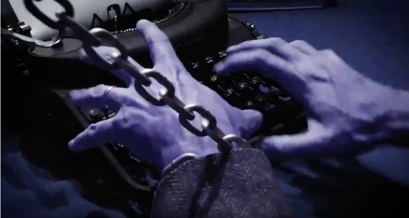 Pair of chained hands hovering over an old fashioned typewriter